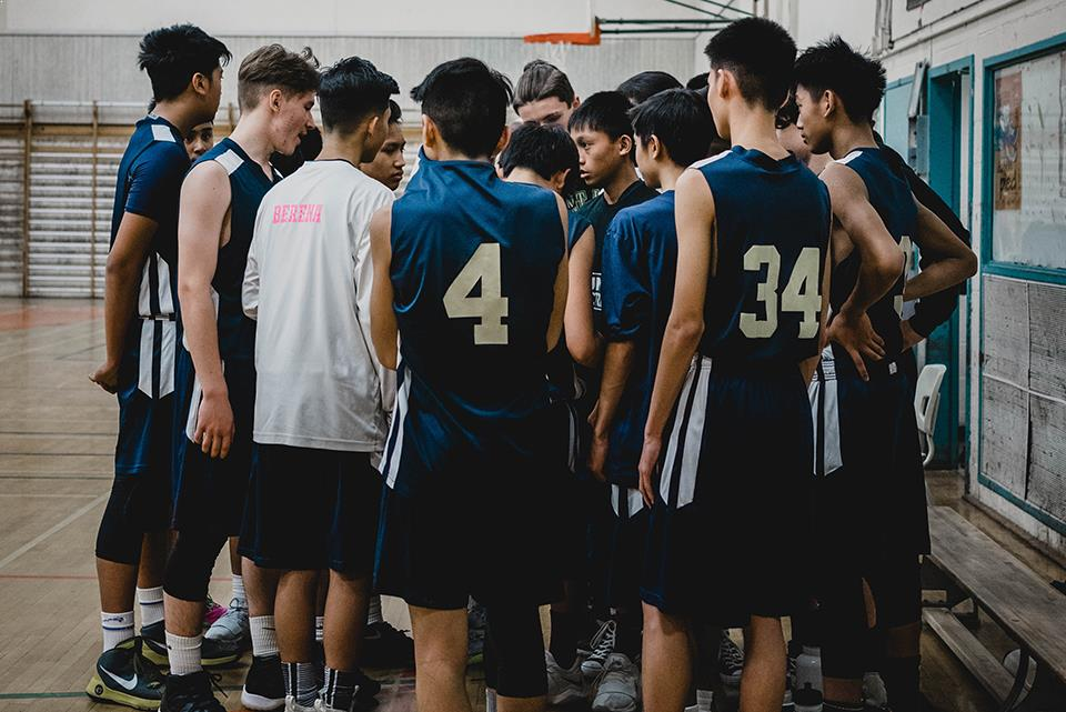 Group of boys in blue sports kit in huddle at basketball game