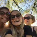 3 girls in sunglasses under trees in the sun