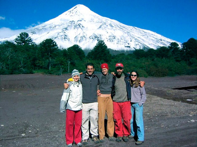 Student with host family in front of mountain