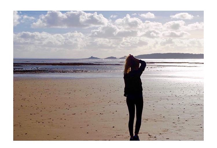 Girl on beach with clouds and sun shining